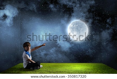 Cute school boy sitting on floor and touching moon with finger