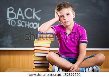 Cute school boy sitting with books against blackboard in classroom - stock photo