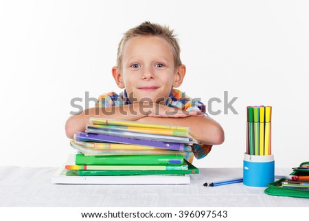 Cute school boy with pile of books