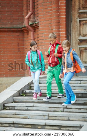 Cute school friends in casual going down stairs - stock photo