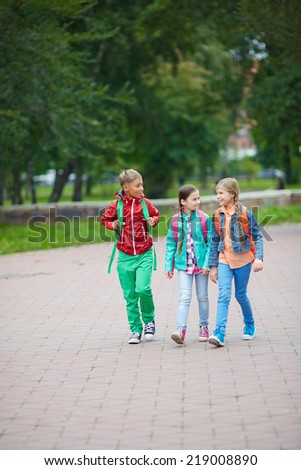 Cute school friends in casual going home through park - stock photo