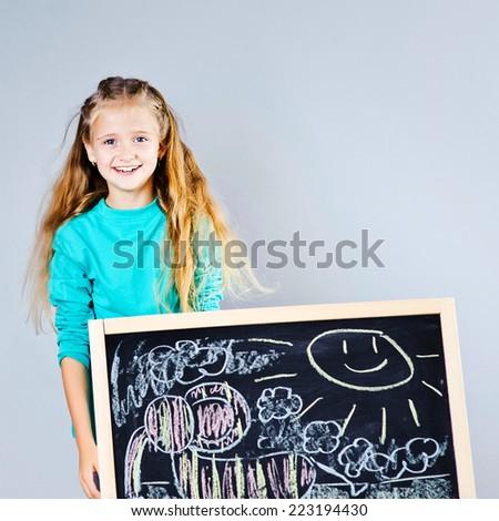 Cute school girl drawing on blackboard - stock photo