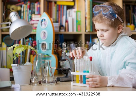 Cute school kid boy sitting at the table making science experiments at home. Learning activities with children at home. Doing water tests. Future profession - scientist. - stock photo