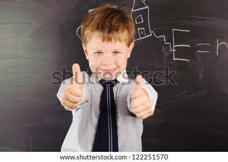Cute schoolboy against dark blackboard in classroom