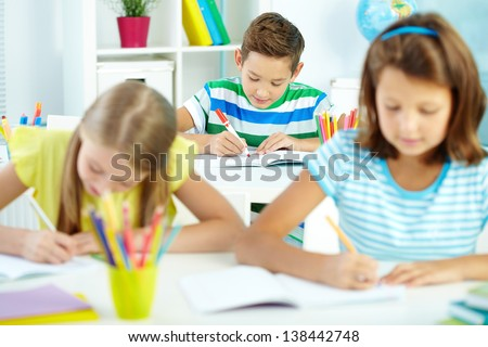 Cute schoolboy drawing at workplace with schoolmates on foreground - stock photo