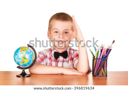 Cute schoolboy, globe and pencils on the table isolated on white background. - stock photo