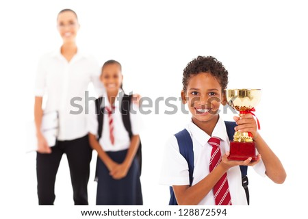 cute schoolboy holding trophy in front of teacher and classmate