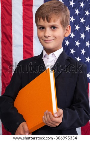 Cute  schoolboy is holding an orange book against USA flag - stock photo