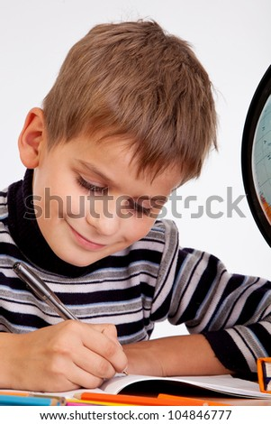 Cute schoolboy is writing isolated on a white background