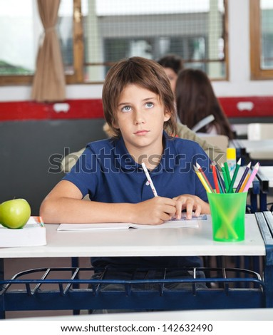 Cute schoolboy looking away while writing at desk in classroom - stock photo