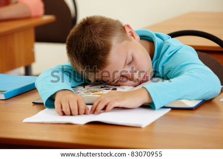 Cute schoolboy lying on book and sleeping in class during lesson - stock photo