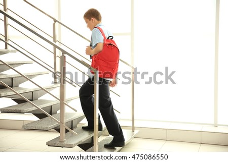 Cute schoolboy on staircases