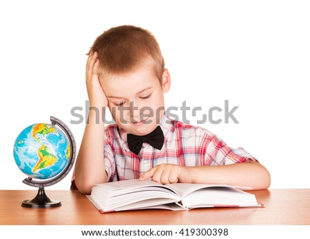 Cute schoolboy reading a book, the globe on the table isolated on white background. - stock photo