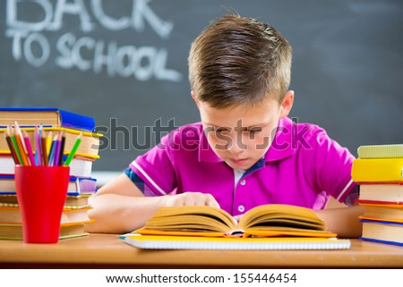 Cute schoolboy reading in classroom foreground blackboard - stock photo