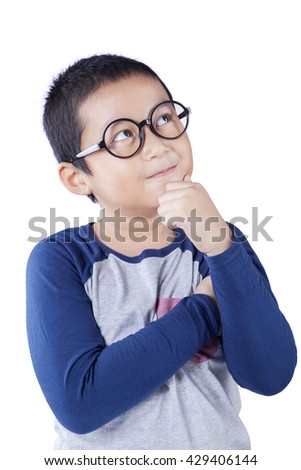 Cute schoolboy thinking idea while wearing glasses and looking at up, isolated on white background