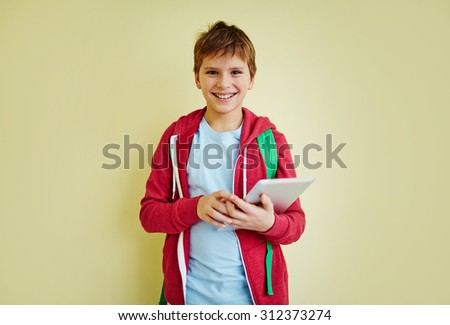 Cute schoolboy with touchpad looking at camera with smile - stock photo
