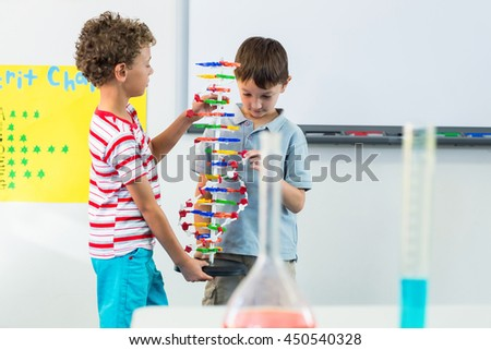Cute schoolboys holding DNA model in classroom - stock photo