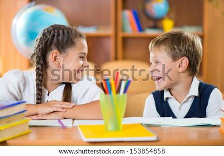 Cute schoolchildren having fun in classroom at school - stock photo