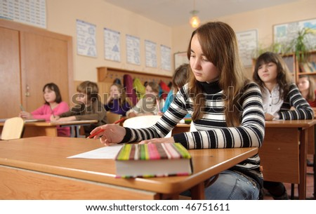 Cute schoolgirl is making notes during lesson - stock photo