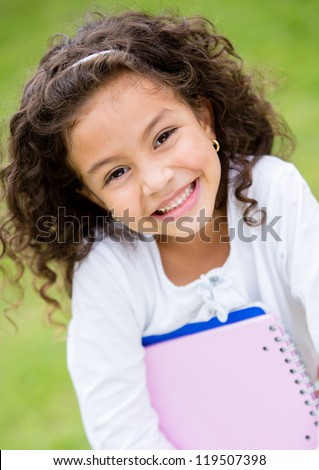 Cute schoolgirl outdoors holding notebooks and smiling - stock photo