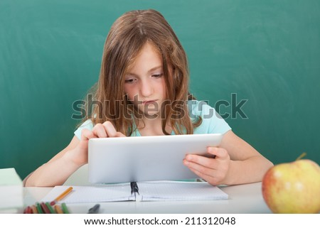 Cute schoolgirl using digital tablet while sitting at table against chalkboard