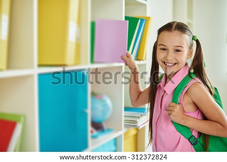 Cute schoolgirl with backpack looking at camera in library - stock photo