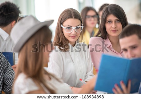 Cute schoolgirl with glasses posing in classroom - stock photo