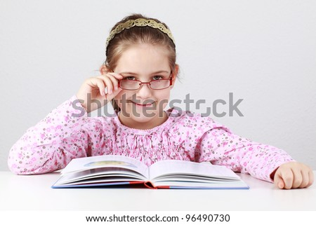 Cute schoolgirl with glasses reading book - stock photo