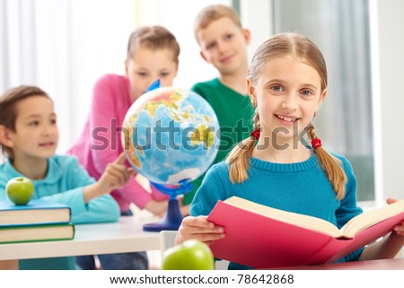 Cute schoolgirl with open book looking at camera on background of her classmates