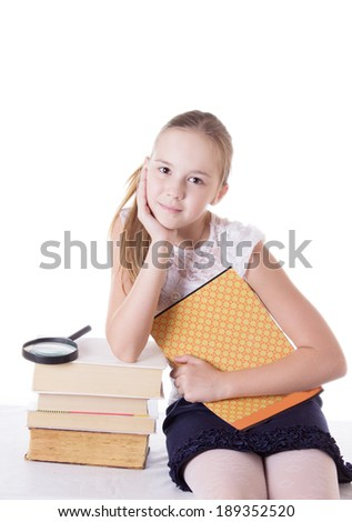 Cute schoolgirl with pile of books isolated on white - stock photo