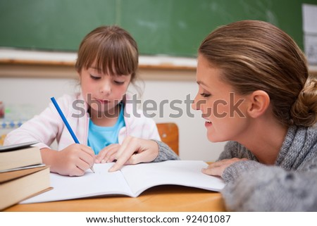 Cute schoolgirl writing a while her teacher is talking in a classroom