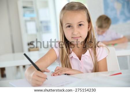 Cute schoolgirl writing on notebook, in classroom - stock photo