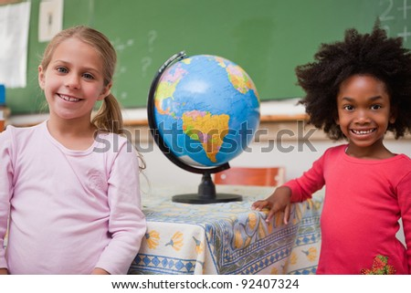Cute schoolgirls posing with a globe in a classroom