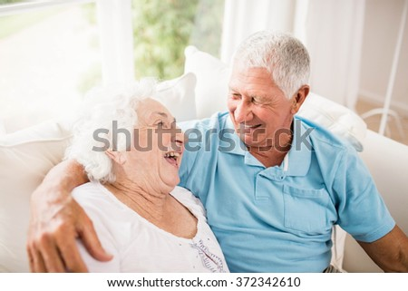 Cute senior couple hugging on sofa - stock photo