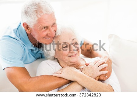 Cute senior couple hugging on sofa - stock photo