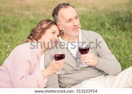 Cute senior married couple is drinking red wine in park. They are sitting and dreaming about future. They are embracing and smiling - stock photo
