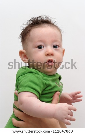 Cute serious baby held by his mother turns toward the camera - stock photo