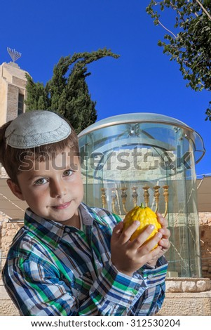 Cute seven year old boy in a white skullcap with the etrog. Sukkot at the Golden Menorah in Jerusalem - stock photo
