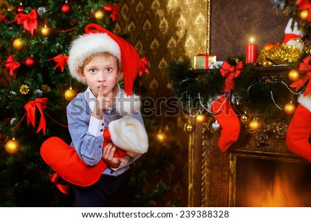 Cute seven year old boy stands with a gift by the Christmas tree at home. The magic of Christmas. - stock photo
