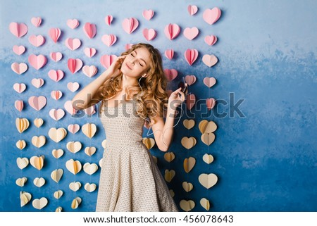 Cute sexy slim girl with blond curly hair standing in a studio with blue background and listening to music on earphones. She smiles and looks sexy.