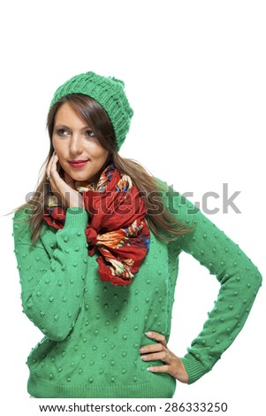 Cute sexy young woman with long brunette hair in a green winter outfit smiling playfully at the camera with her hand to her red scarf, on white