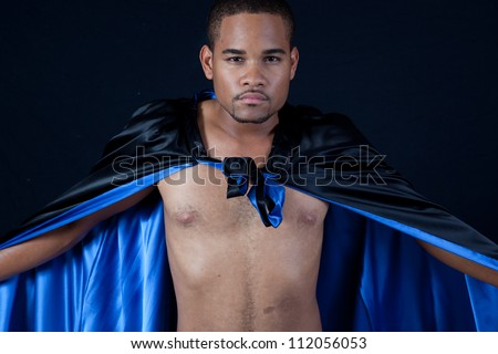 Cute shirtless black man wearing a black cape with blue satin inside, making dramatic statements with his arms and the shiny material