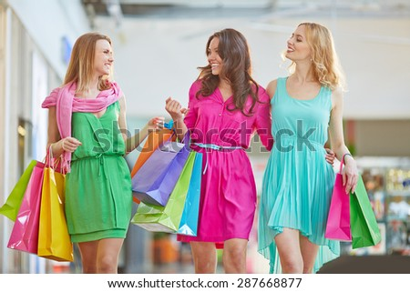 Cute shopaholics with paperbags having talk in the mall