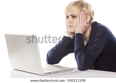 cute short hair blonde indifferently reading the content on the laptop