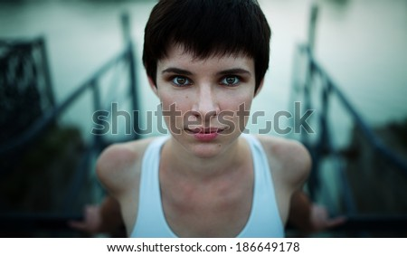 Cute short haired girl  looking strongly to the camera - stock photo