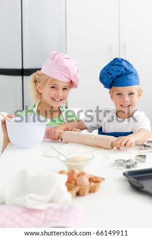 Cute sibling baking cookies together in the kitchen at home