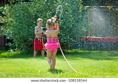 Cute siblings- boy and girl are playing with water on a summer d - stock photo