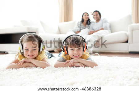 Cute siblings listening music with headphones lying on the floor