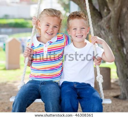 Cute siblings swinging in a park - stock photo