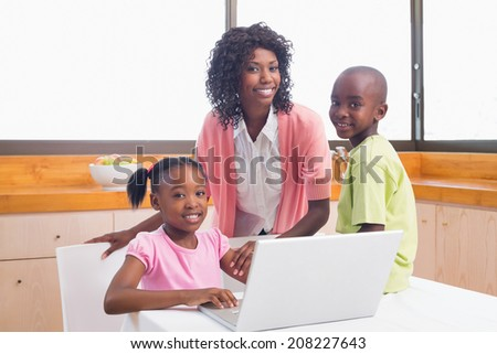 Cute siblings using laptop together with mother at home in the kitchen